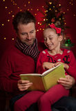 Christmas - smiling father and daughter reading a book Stock Photos