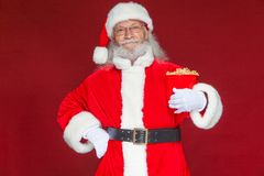Christmas. Smiling, kind Santa Claus in white gloves holds a red bucket with popcorn with one hand, and puts the other. Hand on his belt. The concept of stock photos
