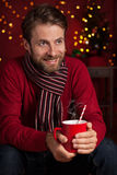 Christmas - smiling man holds hot drink or cocoa cup Stock Images