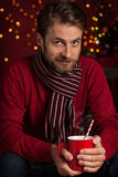 Christmas - smiling man holds hot drink or cocoa cup Royalty Free Stock Photos