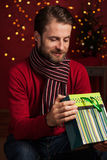 Christmas - smiling man opens gift bag on dark red with lights Royalty Free Stock Photos