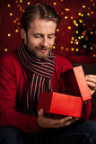 Christmas - smiling man opens present on dark red with lights Stock Photo