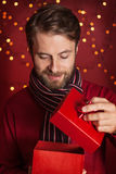 Christmas - smiling man opens present on dark red with lights Stock Image