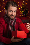 Christmas - smiling man opens present on dark red with lights Royalty Free Stock Image