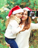 Christmas smiling mother and child taking picture self portrait on smartphone together. Over snowflakes Stock Image