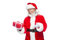 Christmas. Smiling Santa Claus in white gloves is holding a gift red box with a bow. Pointing at the gift. Isolated on Stock Photography