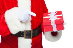 Christmas. Smiling Santa Claus in white gloves is holding a gift red box with a bow. Pointing at the gift. Isolated on Stock Images