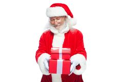 Christmas. Smiling Santa Claus in white gloves is holding two gift red boxes with a bow, one on the other. Isolated on Royalty Free Stock Photography