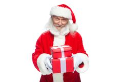 Christmas. Smiling Santa Claus in white gloves is holding two gift red boxes with a bow, one on the other. Isolated on Stock Photos