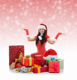 Christmas Smiling Woman. In red santa cap with a gift Stock Photos
