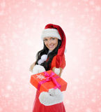 Christmas Smiling Woman. In red santa cap with a gift Royalty Free Stock Images