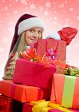 Christmas Smiling Woman. In red santa cap with a gift Royalty Free Stock Photo