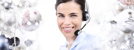 Christmas smiling woman with headset on christmas balls. Background Royalty Free Stock Photo