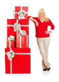 Christmas: Smiling Woman Leans On Stack Of Red Christmas Gifts Stock Image