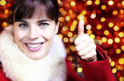 Christmas smiling woman like hand with thumb up on blurred brigh. T lights background Royalty Free Stock Photos