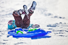 Christmas Snow Fun. A little girl having fun falling off a blue sled on  Christmas Day at St Cergue, Switzerland Stock Image