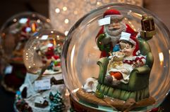 Christmas snow glass balls with seasonal decorations. CLoseup of seasonal Christmas decorations, glass balls or bowls with santa claus, dwarves, snowy figurines Stock Image