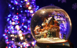 Christmas Snow Globe. Santa Snow Globe upclose with christmas tree in background stock images