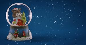 Christmas Snow Globe. With little bear on light blue background stock footage
