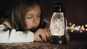 Christmas snow globe and cute girl watching snowflakes and lights stock video footage