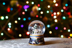 Christmas Snow Globe in front of Christmas tree lights closeup Royalty Free Stock Photography