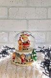 Christmas snow globe with santa claus inside and garland lights Stock Photos