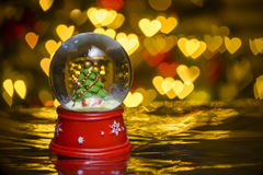 Christmas snow globe with xmas lights in background;. Decorated christmas tree; heart shapes bokeh blur Stock Photos