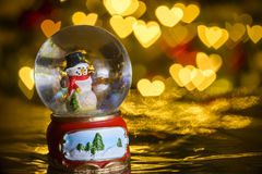 Christmas snow globe with xmas lights in background;. Snowman with presents; heart shapes, bokeh blur Royalty Free Stock Image