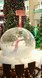 Christmas Snow man in snow globe. Tree mall lighting trinkets Royalty Free Stock Photo