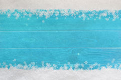 Christmas Snowflake Border on Blue Wood. Christmas snow and snowflakes border at top and bottom of light, bright blue wood planking royalty free stock image