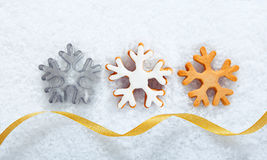 Christmas snowflake cookies on snow. Christmas cookies in the shape of ornate snowflakes lying in a line on snow with a decorative gold ribbon for your seasonal Royalty Free Stock Photo