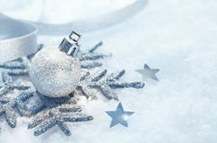 Christmas snowflake ornament on snow. A silver Christmas snowflake ornament and bauble in fresh snow with scattered stars and copyspace for your seasonal Stock Photography