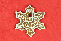 Christmas snowflake shape gingerbread on red background Royalty Free Stock Photos