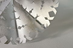 Christmas snowflake. The silver snowflake  cut out of paper on snow background Stock Image