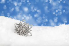 Christmas Snowflake. A silver Christmas snowflake in drift of snow with blue sky and bokeh background Royalty Free Stock Photos