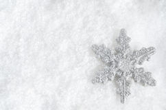 Christmas Snowflake on Snow. Winter background shot from above.  Glittery silver Christmas snowflake faces upwards on lower right, lying in fake snow Stock Photo