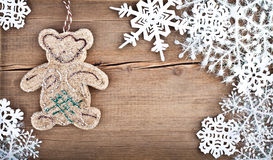 Christmas snowflakes and bear toy on wooden background Stock Image