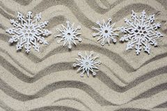 Christmas snowflakes lie on the beach sand stock images
