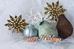 Christmas Snowflakes and ornaments. On a brocade background with Happy Holidays across the bottom Stock Photo