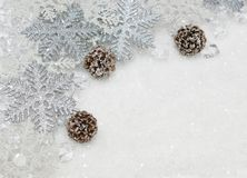 Christmas snowflakes and pine cones nestled in snow. Christmas silver glitter snowflakes and pine cones nestled in snow Stock Photo