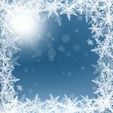 Christmas snowflakes and sun on blue background. Stock Photography