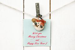 Christmas snowman clothespins holding greeting note paper Royalty Free Stock Image