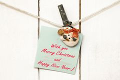 Christmas snowman clothespins holding greeting note paper Royalty Free Stock Images