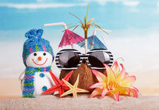 Christmas snowman, coconut glasses, flowers and starfish in the sand Stock Photos