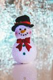 Christmas snowman decoration doll on top of a table. Casting a reflection Stock Photos