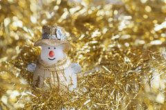 Christmas snowman decoration on gold sparkles. Backgraund Stock Images