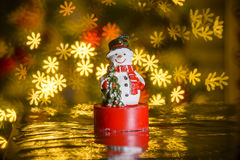 Christmas snowman and flower shaped lights in background Royalty Free Stock Image