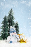 Christmas snowman with gifts on snowy background Stock Photo