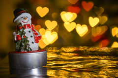 Christmas snowman and heart shaped lights in background Stock Photos