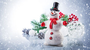 Christmas snowman. Holiday greeting card copyspace. Fairy-tale personage with branch tree and balls. Decoration winter still life. Falling snow Stock Images